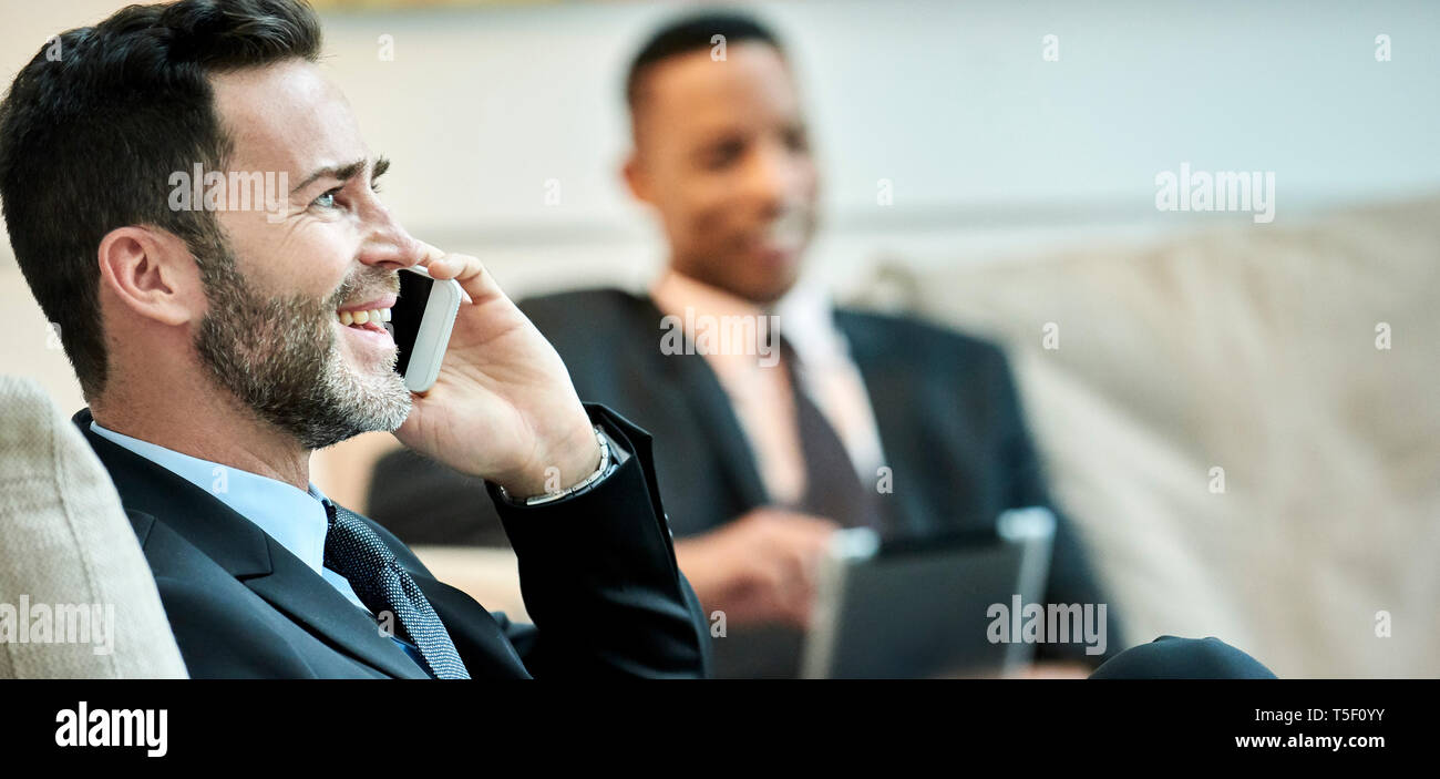 Businessman using smart phone in hotel lobby - Stock Image