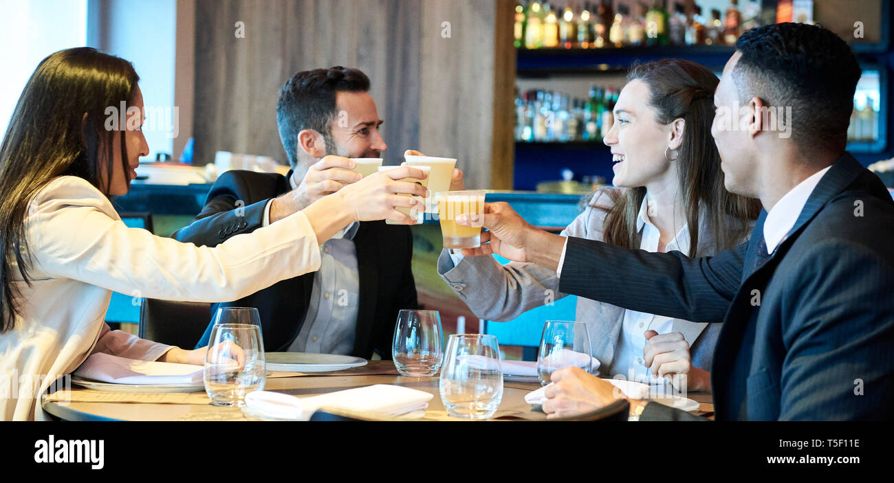 Business people toasting drink in bar - Stock Image