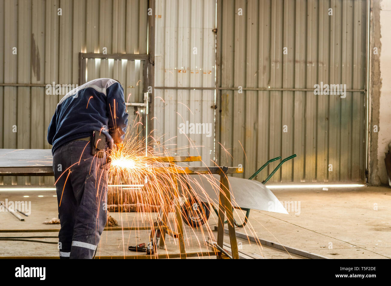 Heavy industry manual worker cutting metal with grinder in factory. - Stock Image