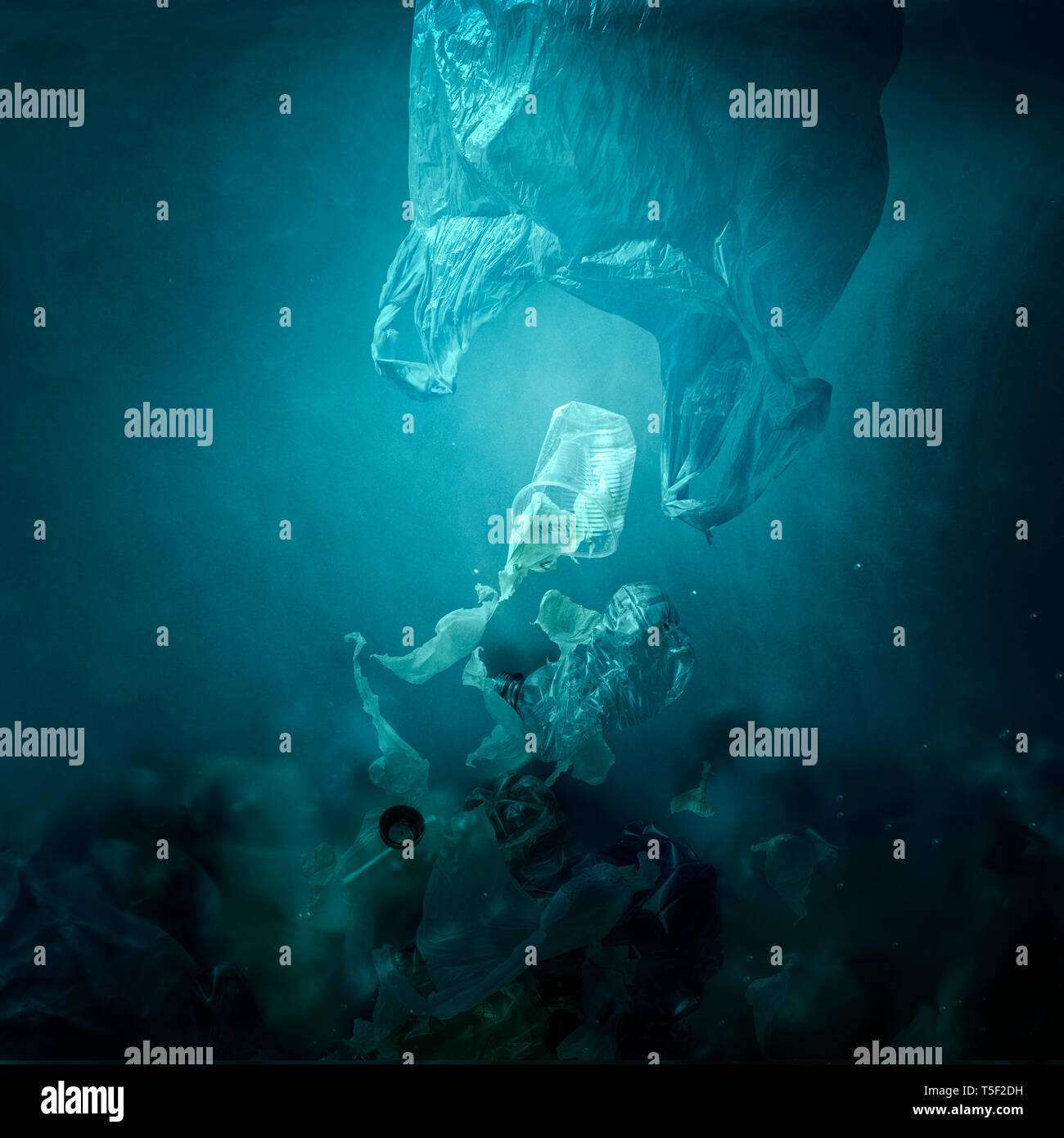 Plastic bag floating underwater and dispersing waste, ocean pollution and environmental damage concept - Stock Image