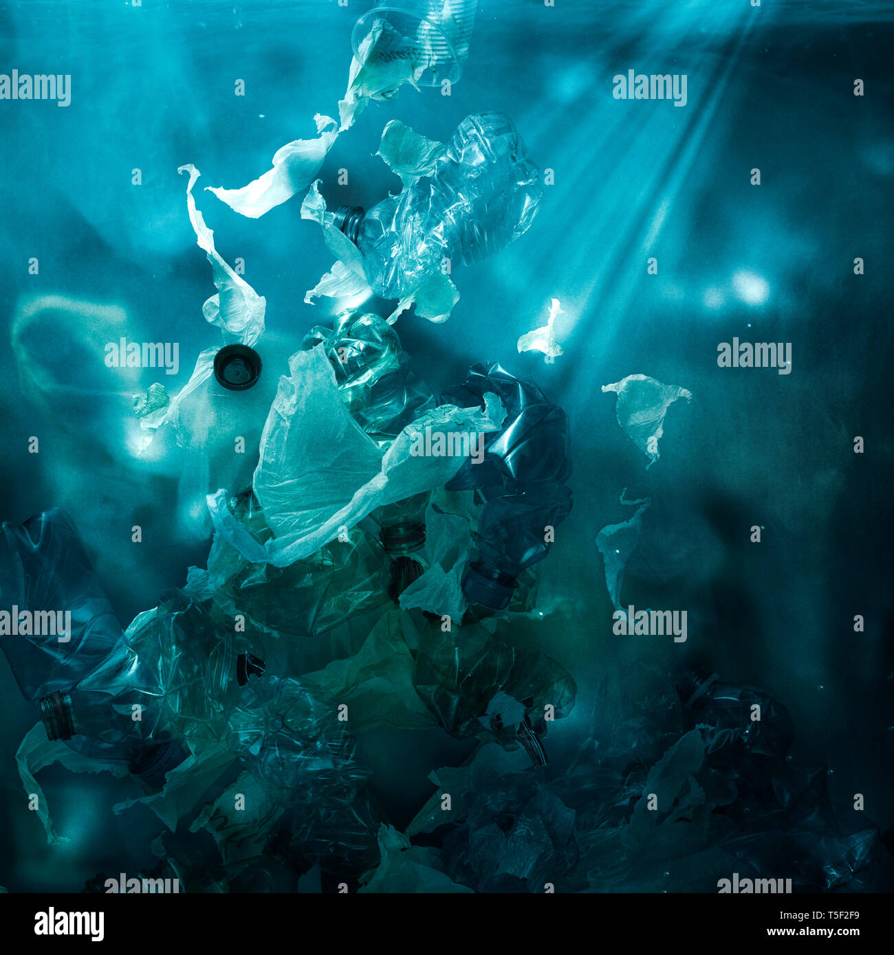 Toxic plastic waste floating underwater in the ocean, water pollution and environmental damage concept - Stock Image