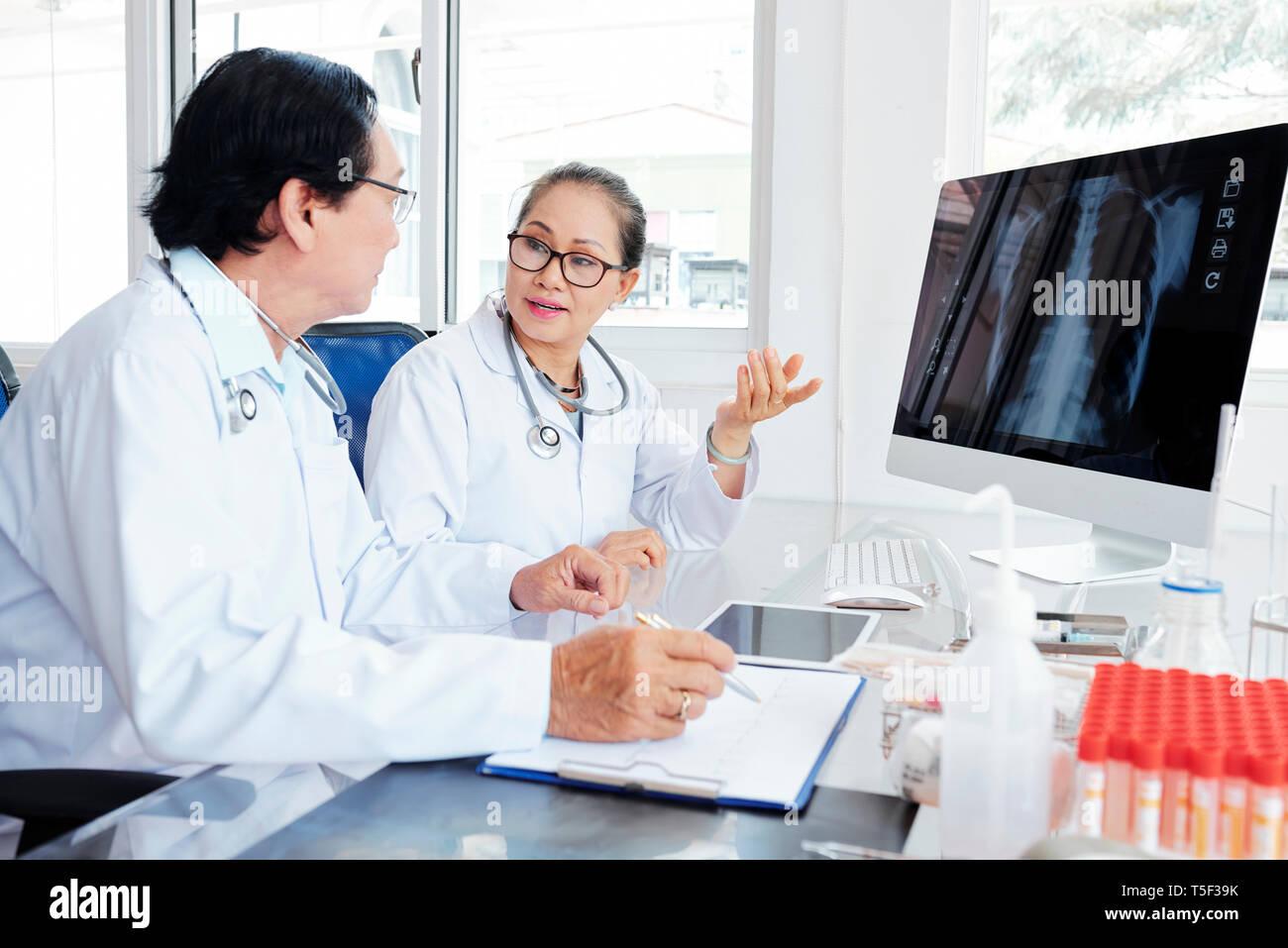 Doctors discussing case of pneumonia - Stock Image