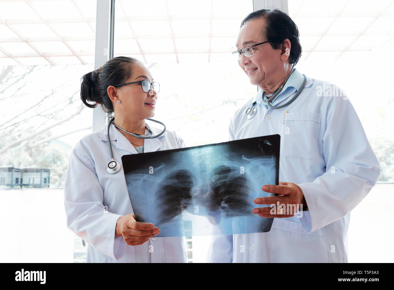 Smiling doctors with x-ray of recovered patient - Stock Image