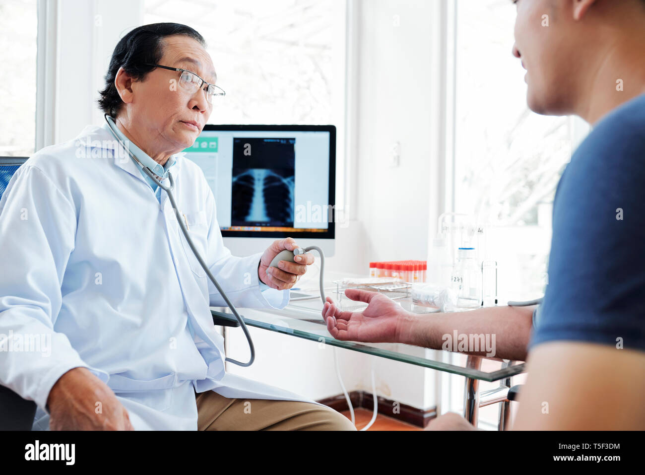 Doctor measuring blood pressure of patient - Stock Image