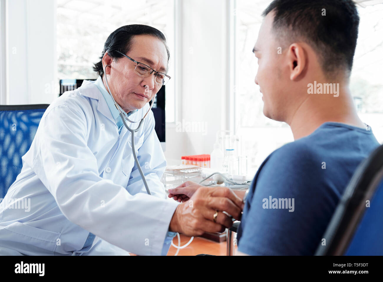 Doctor checking heartbeat of patient - Stock Image