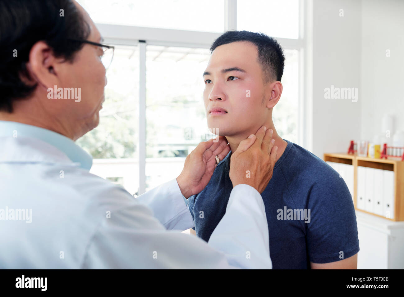 Endocrynologist checking thyroid of patient - Stock Image