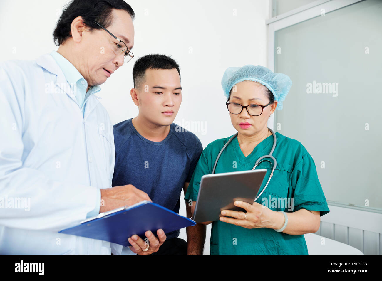 Doctor and surgeon talking to patient - Stock Image