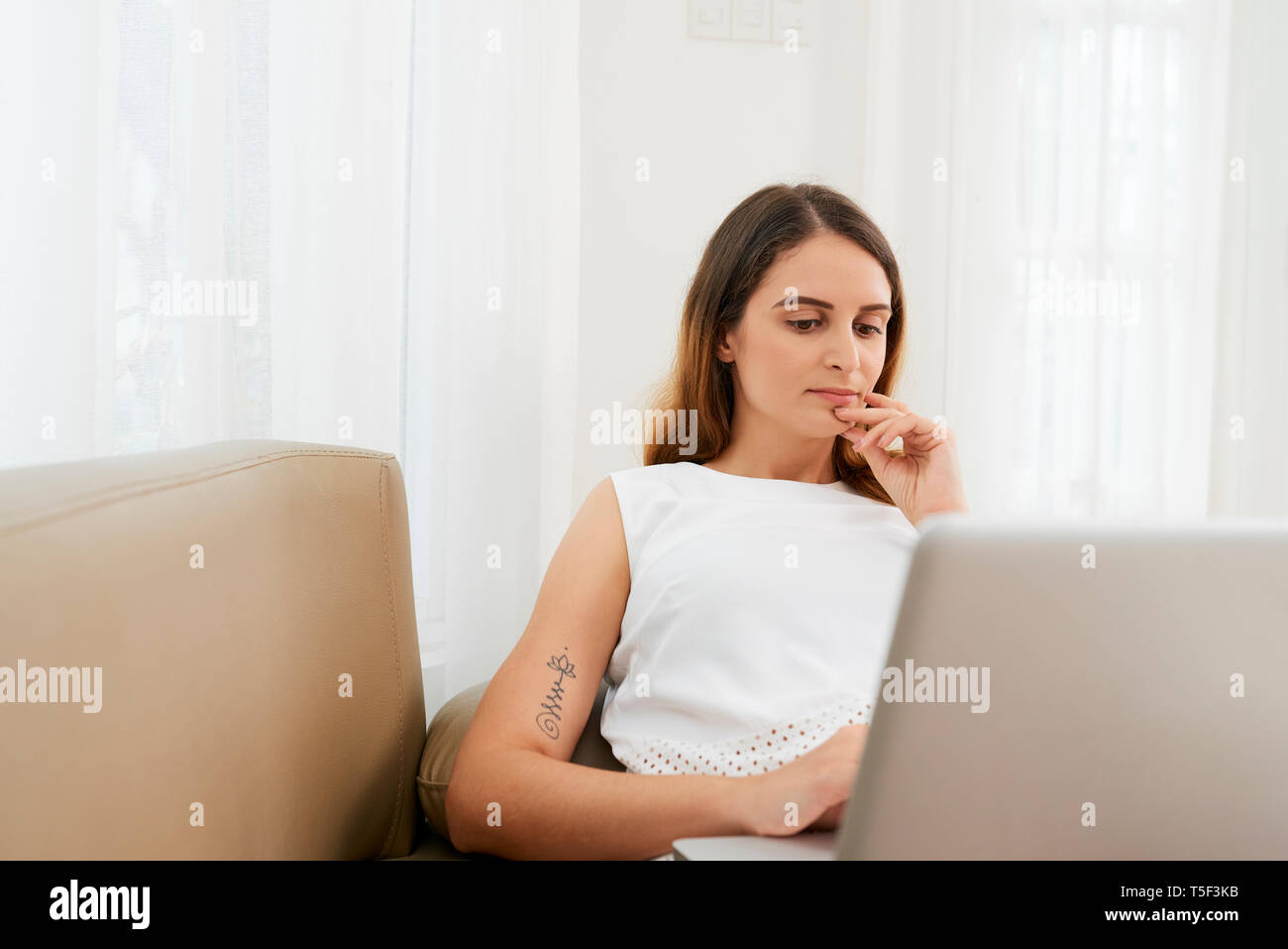 Pensive woman working on laptop - Stock Image