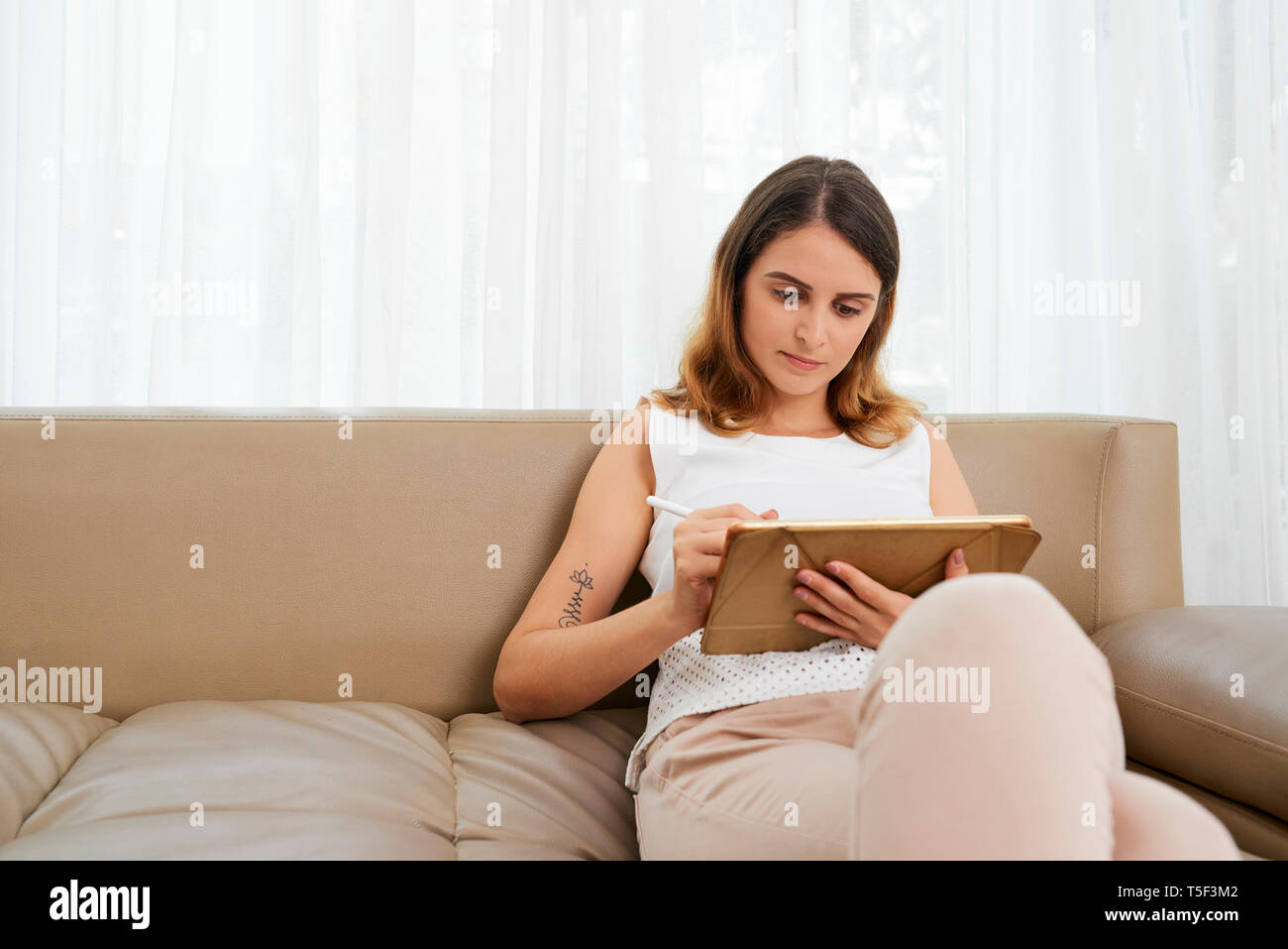 Woman drawing on tablet computer - Stock Image