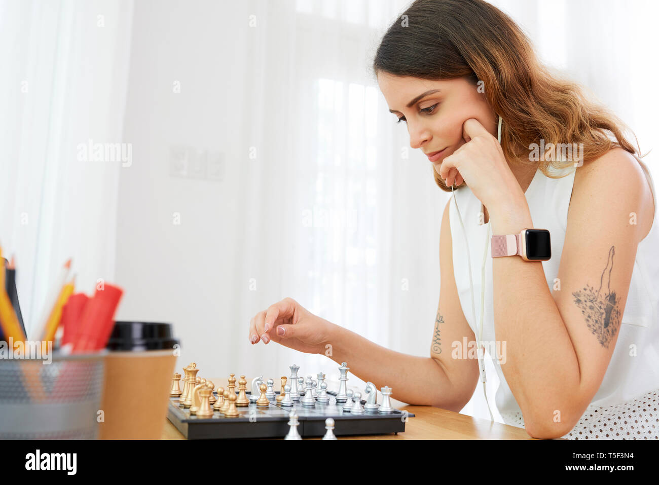 Pensive woman playing chess - Stock Image
