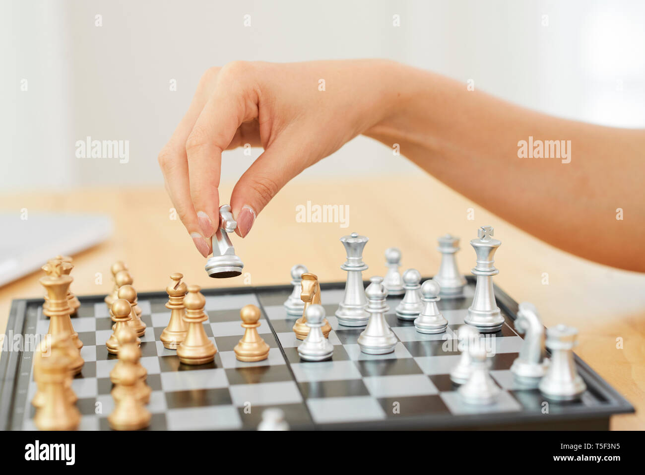 Hand of woman playing chess - Stock Image
