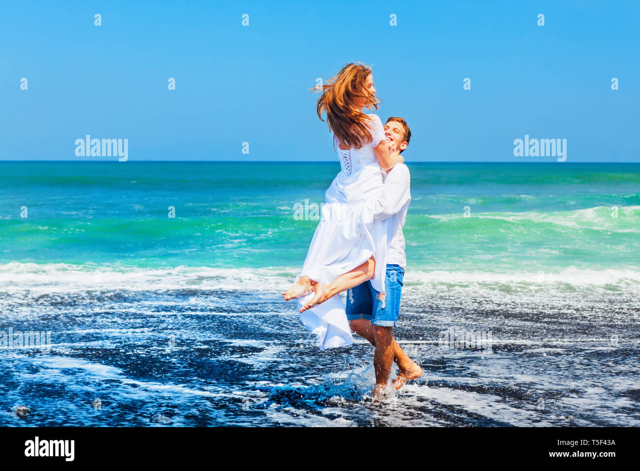 Happy family on honeymoon holiday - just married young man and woman have fun on black sand beach. Active lifestyle, people outdoor activity on summer - Stock Image