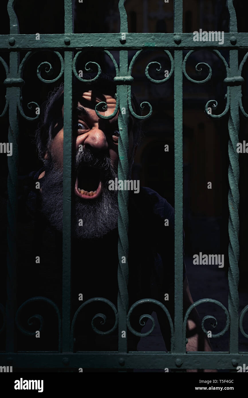 Angry mad man with beard shouting in the dark behind wrought iron fence - Stock Image