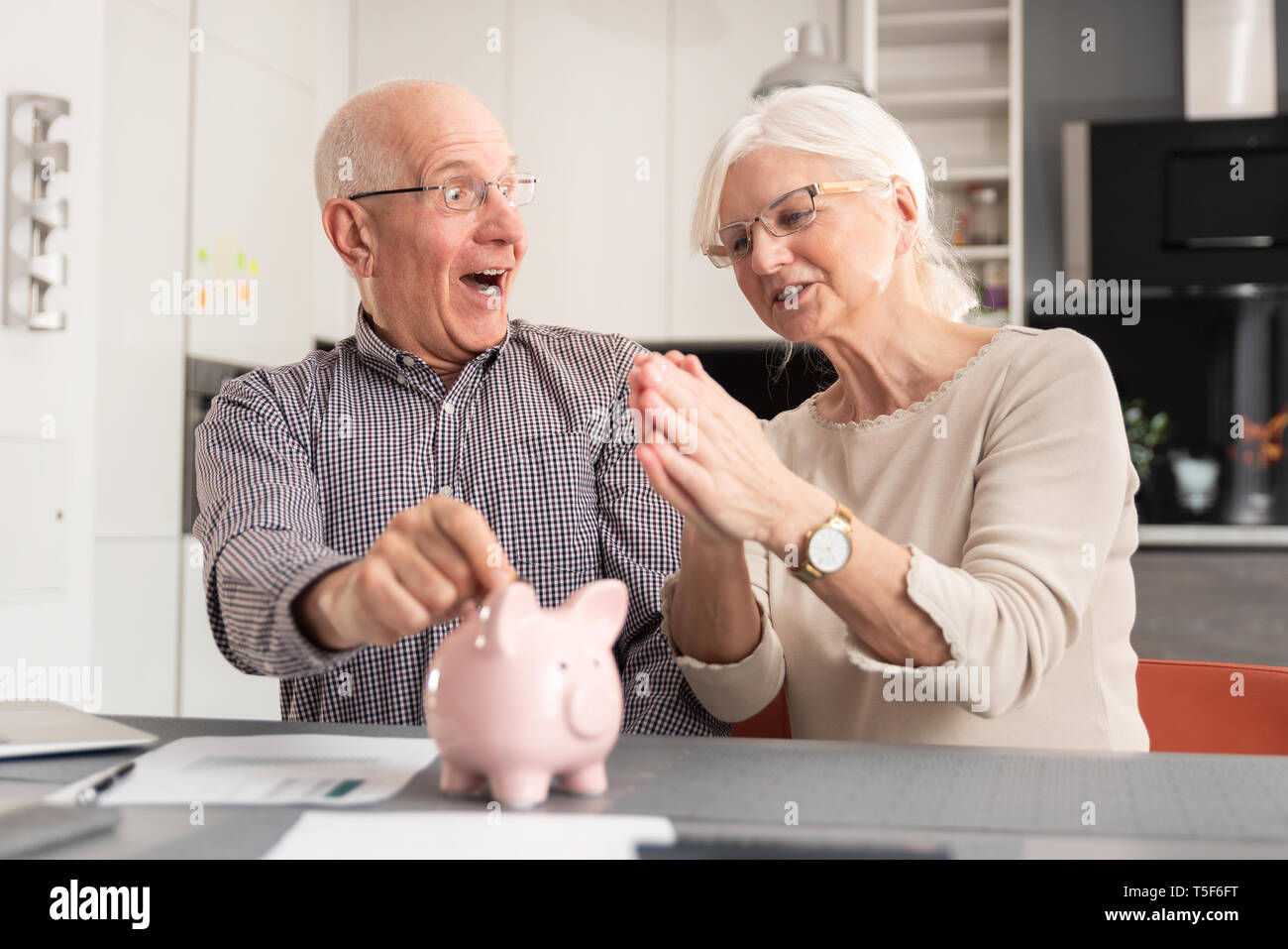 Funny photo of mature couple putting coin into piggy bank at home. Savings, pension plan concept - Stock Image