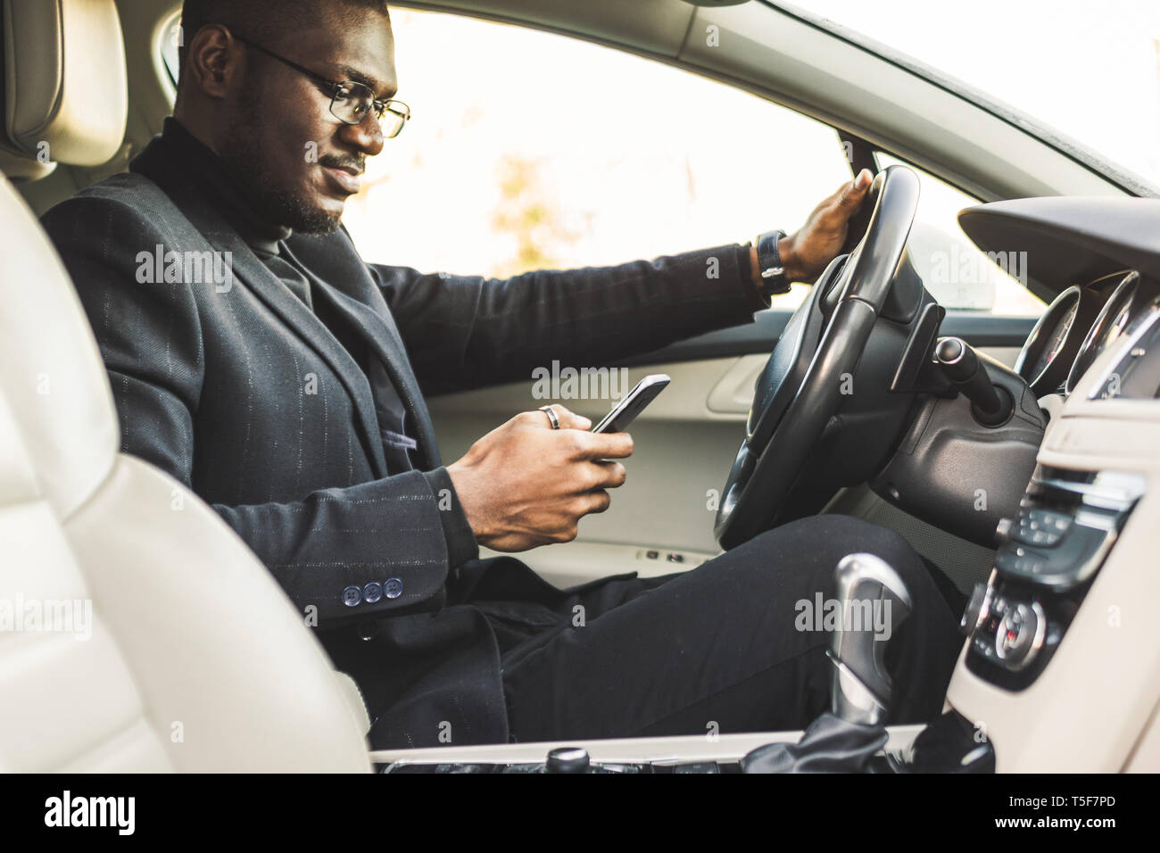 A businessman driving a expensive car holds a mobile phone in his hand. Hasty life. - Stock Image