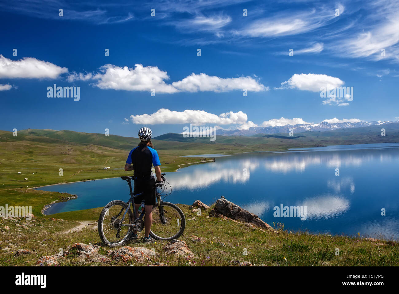 A young man with a bicycle on the background of the high mountain lake Sonkol. Kyrgystan. View from the back - Stock Image