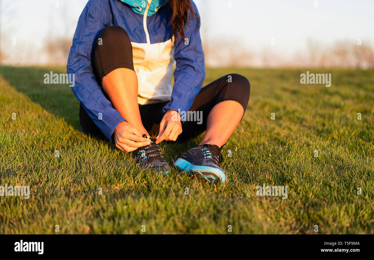 Young woman tying shoelace of sneakers to make outwork training running. Fitness and healthy lifestyle Stock Photo