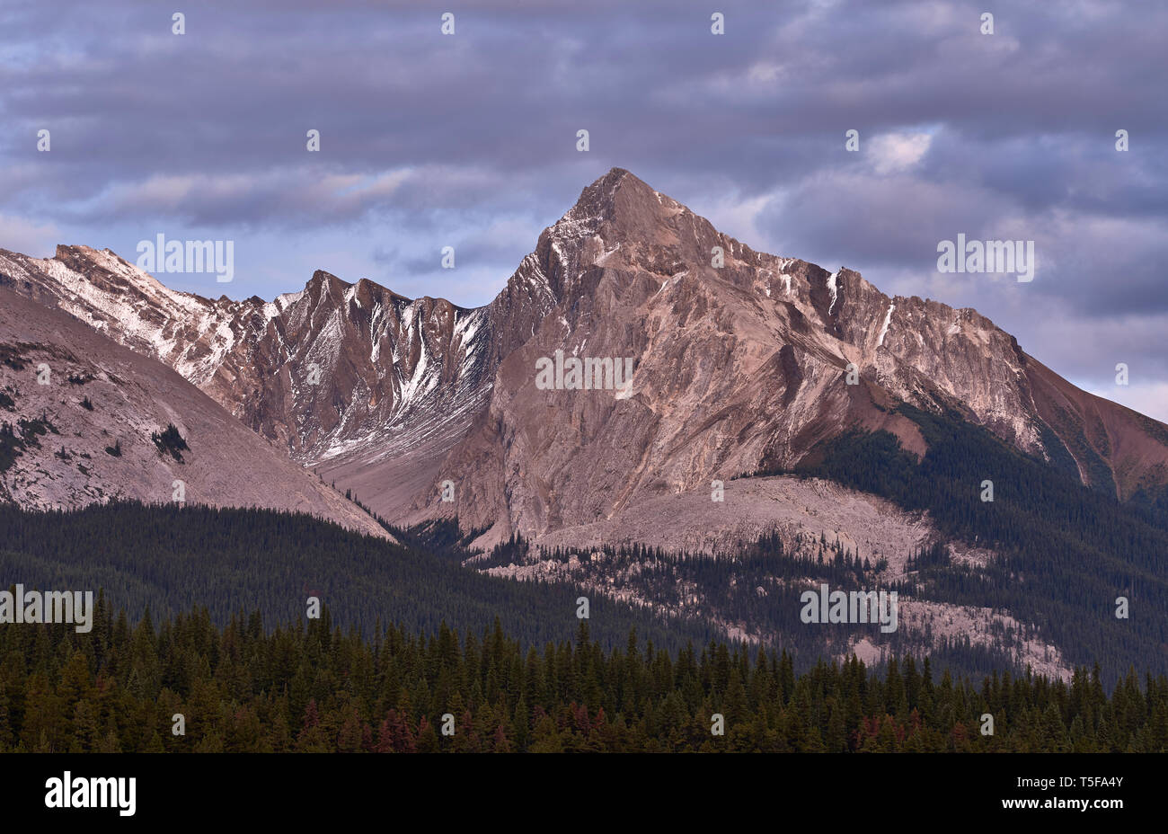 Scenic view of mountains in Maligne lake by snowcapped mountain agains - Stock Image