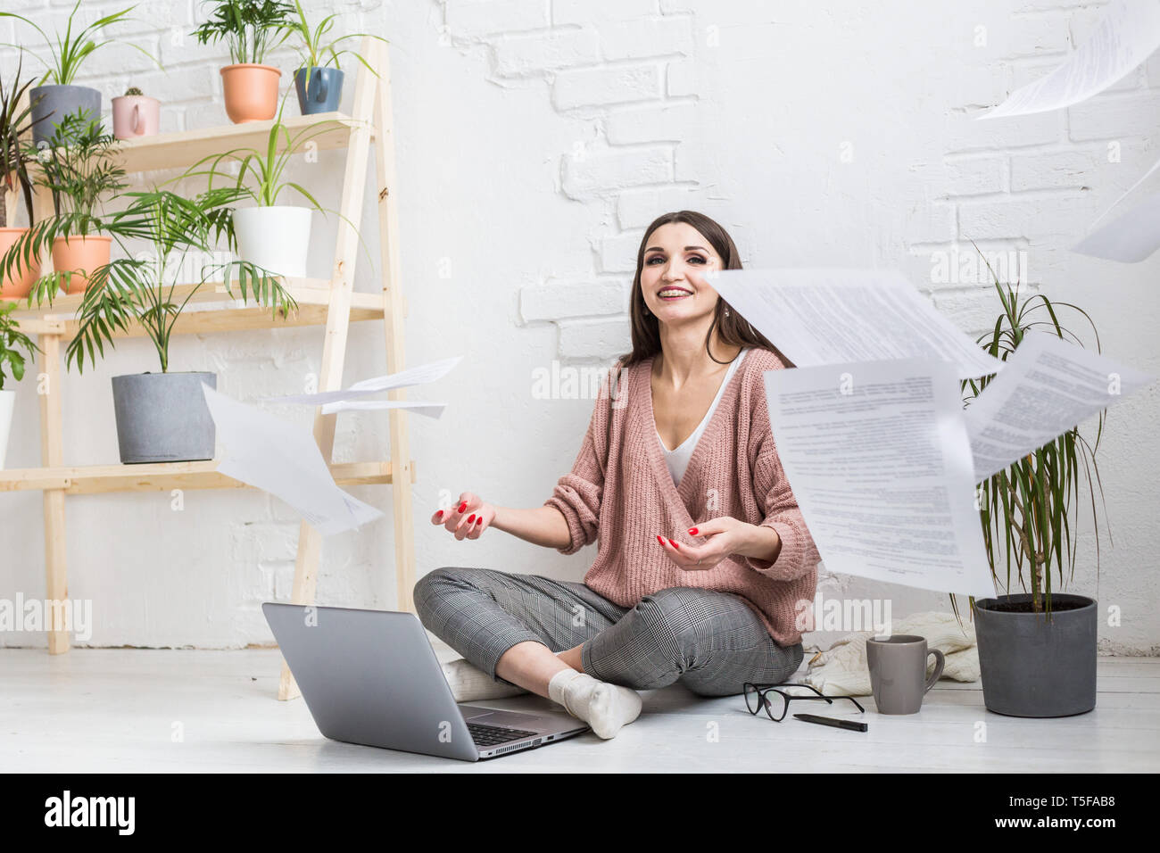 A young happy woman throws up a bunch of pieces of paper and documents sitting near the laptop, the freelance girl is happy and in a good mood Stock Photo