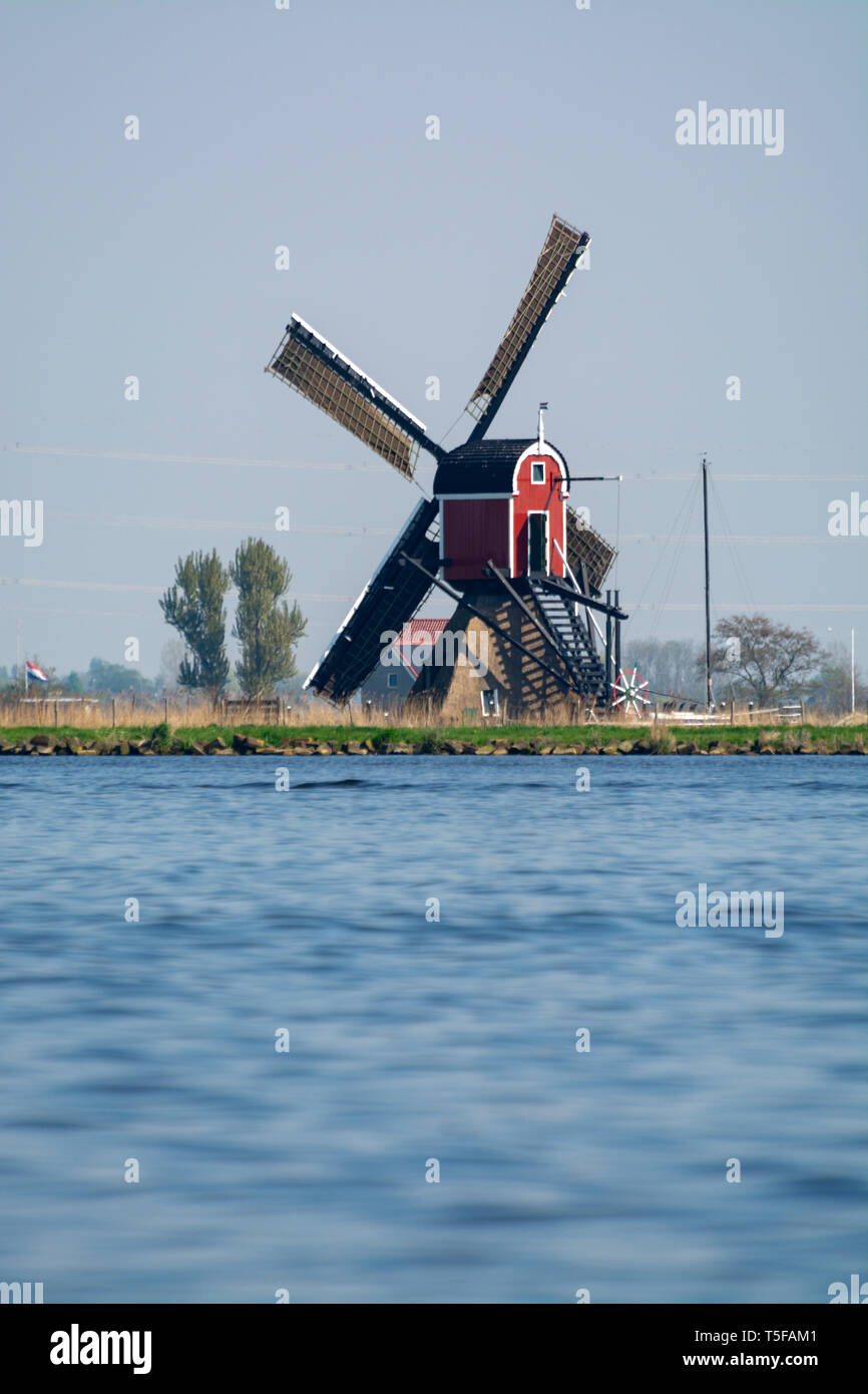 Waterways of North Holland and view on traditional Dutch wind mill, Dutch lifestyle landscape Stock Photo