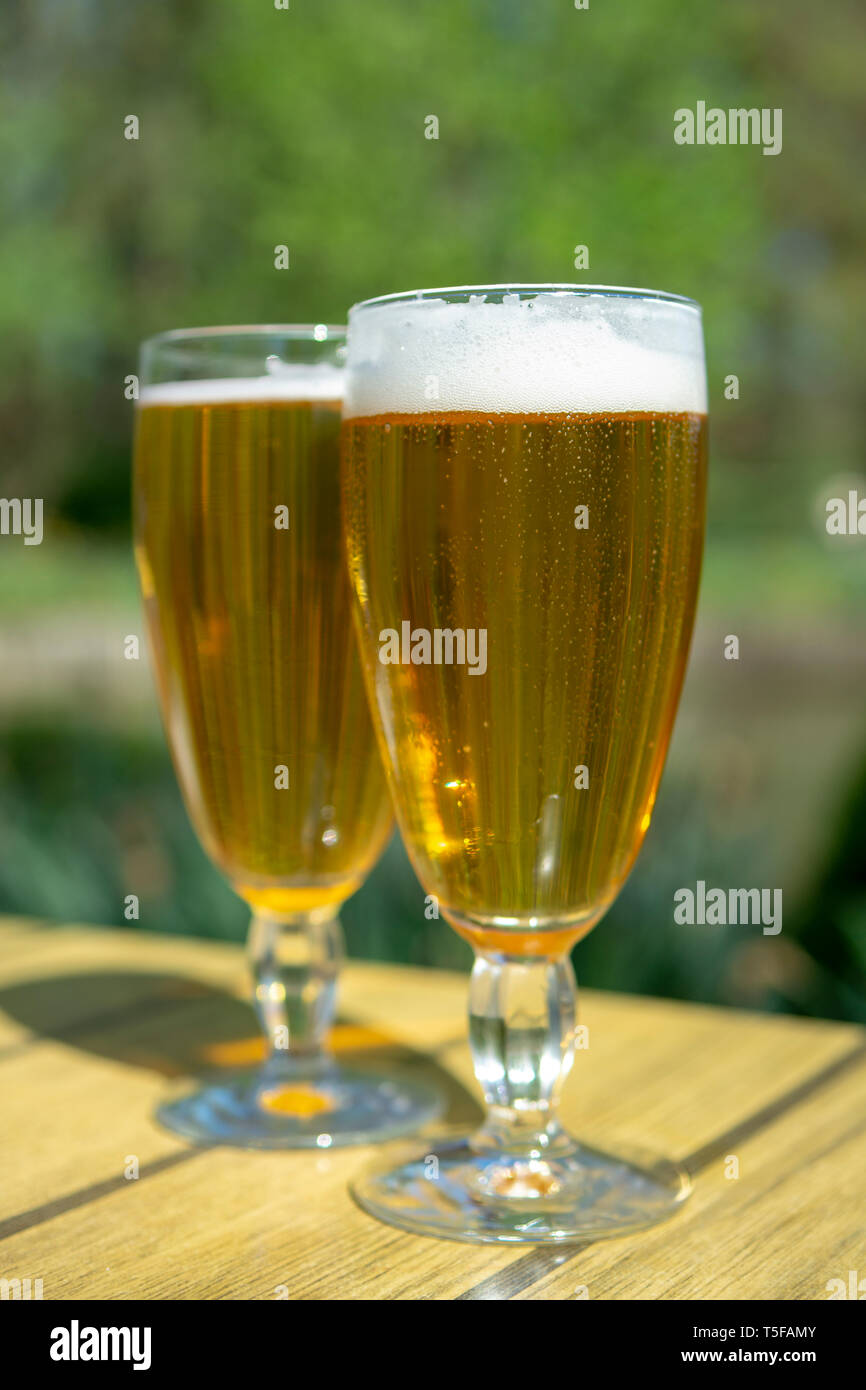 Cold Belgian white beer in glass served outside in sunny day Stock Photo