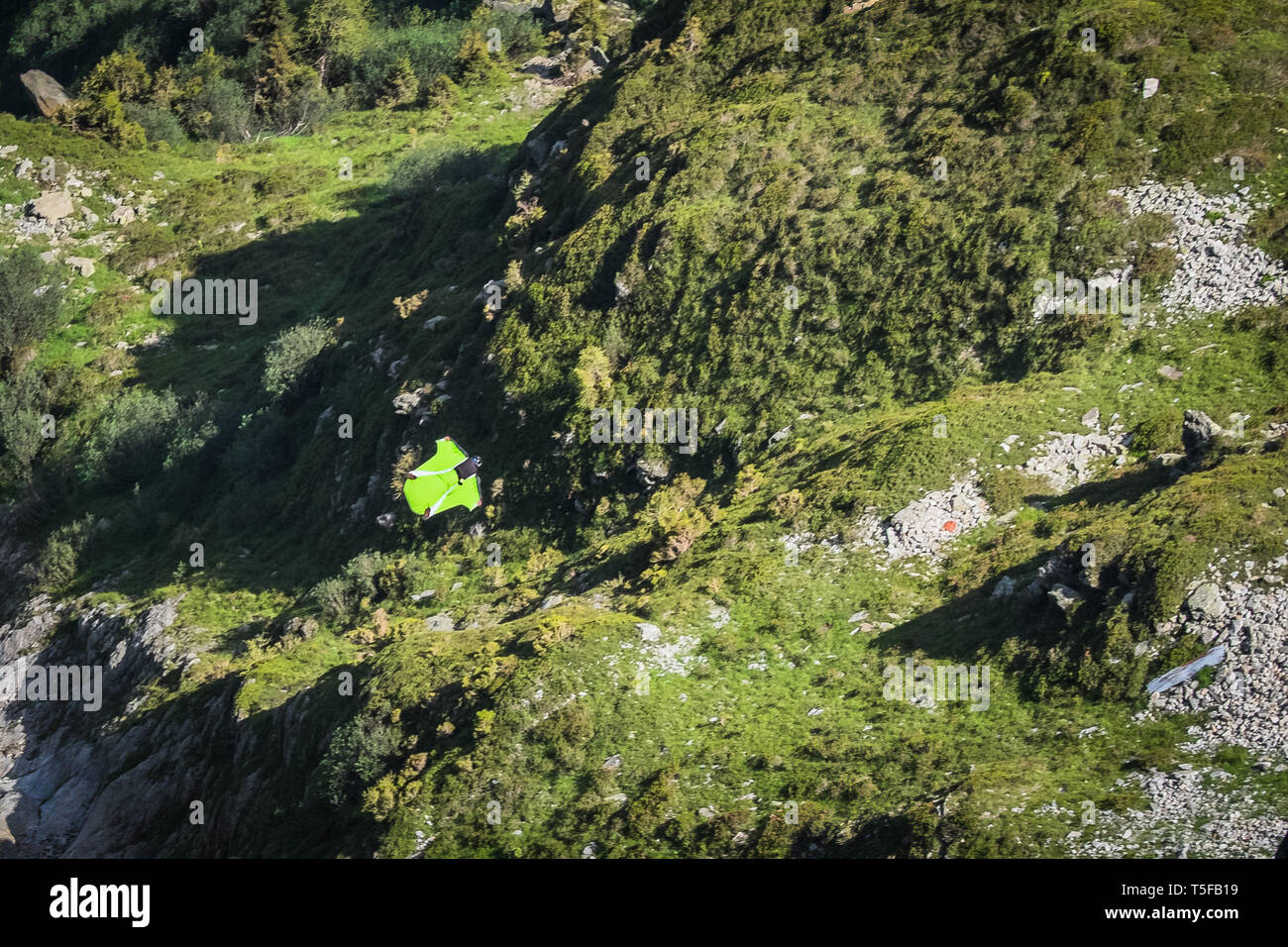 CHAMONIX, FRANCE - JULY 04: A wingsuit jumper jumping from a cliff in france, Auvergne-rhône-alpes, Chamonix, France on July 4, 2015 in Chamonix, France. (Photo by Fred Marie/Art in All of Us/Corbis via Getty Images) - Stock Image