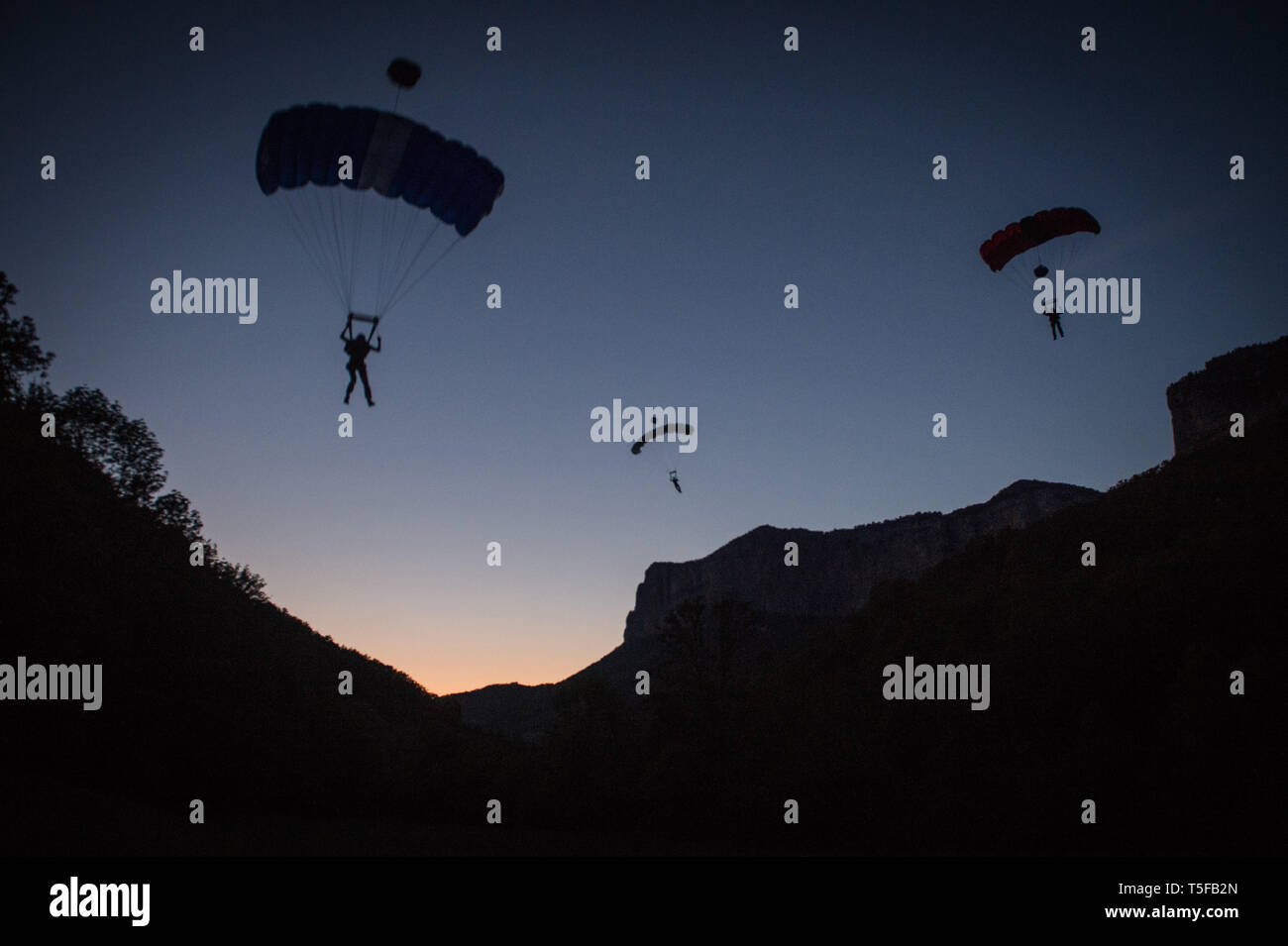 CHORANCHE, FRANCE - AUGUST 21: Three people with a parachute jumping from a cliff in france, Auvergne-rhône-alpes, Choranche, France on August 21, 2015 in Choranche, France. (Photo by Fred Marie/Art in All of Us/Corbis via Getty Images) - Stock Image