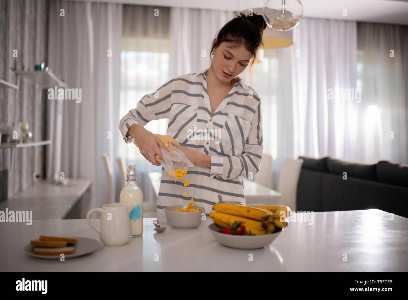 Woman In Sleepwear Preparing Breakfast at her home - Stock Image