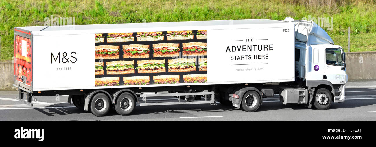 Side view of M&S hgv food supply chain Gist lorry truck & advertising for Marks and Spencer sandwich on articulated trailer driving on UK motorway - Stock Image