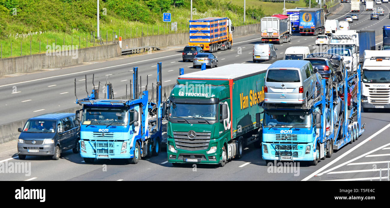 Looking down on hgv lorry truck & articulated trailer vehicles overtaking in  bunched up traffic on gradient busy four lane M25 motorway  England UK - Stock Image
