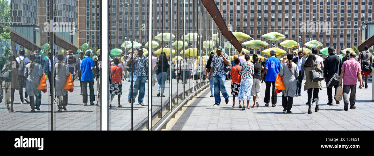 Reflection of group of multicultural people wide footbridge walking to & from entrance Westfield East London shopping centre Stratford City Newham UK - Stock Image