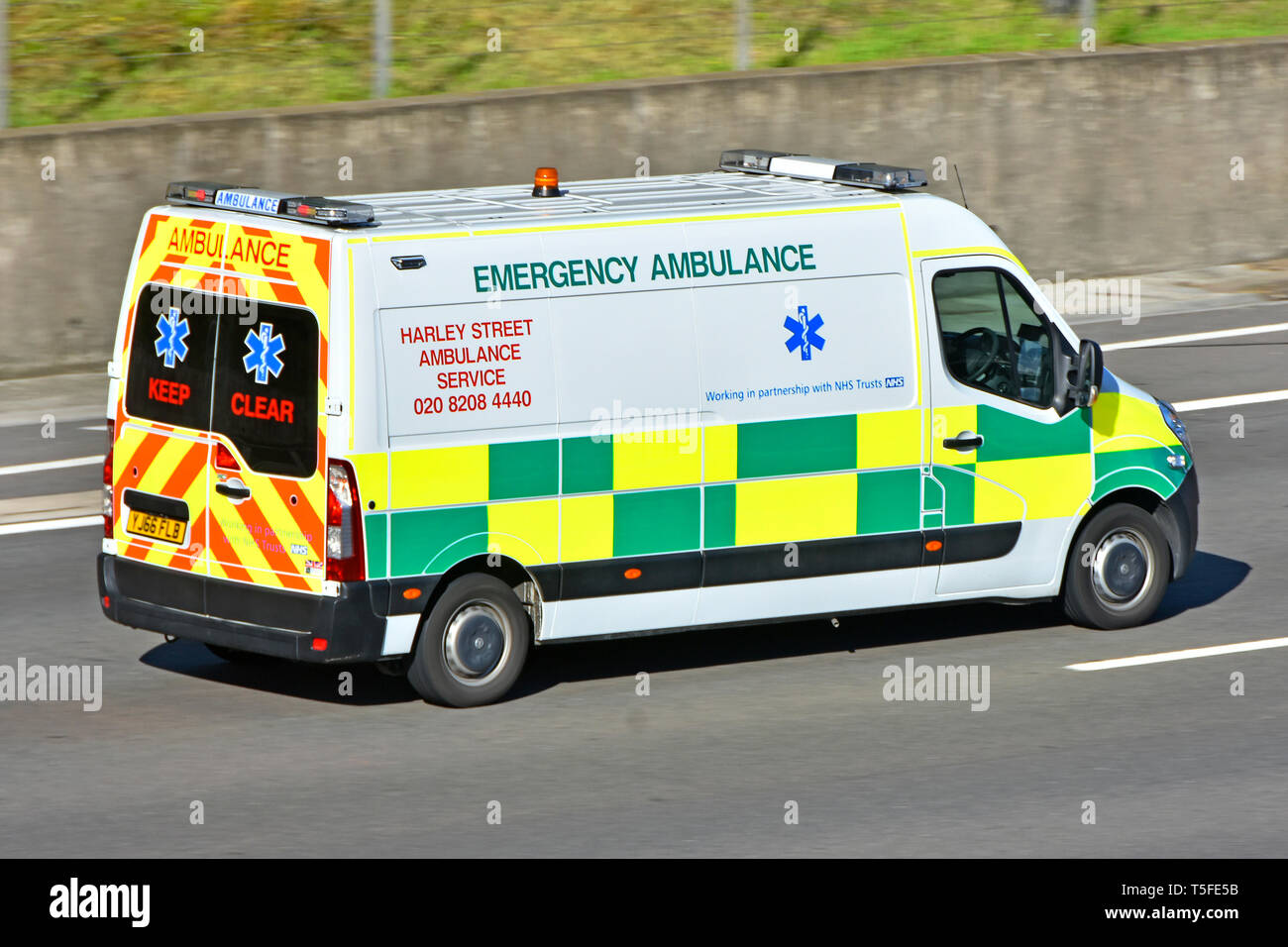 Harley Street private emergency ambulance service vehicle working in partnership with NHS healthcare trusts driving along M25 motorway England UK - Stock Image