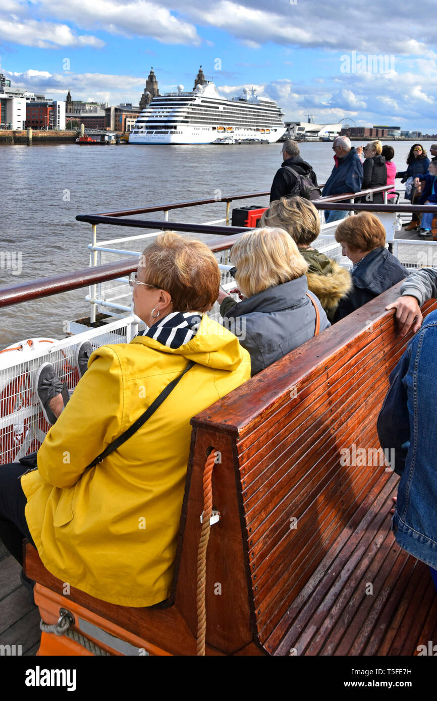 Group of people on Mersey Ferries ferry boat nears Liverpool Pier Head on river crossing from Wirral cruise ship terminal beyond Merseyside England UK - Stock Image