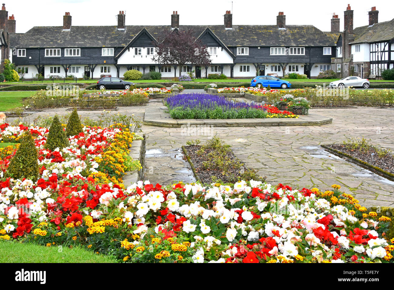 Terraced housing in Port Sunlight model village flowers in public garden all built by Lever Brothers for factory workers  Wirral Merseyside England UK - Stock Image