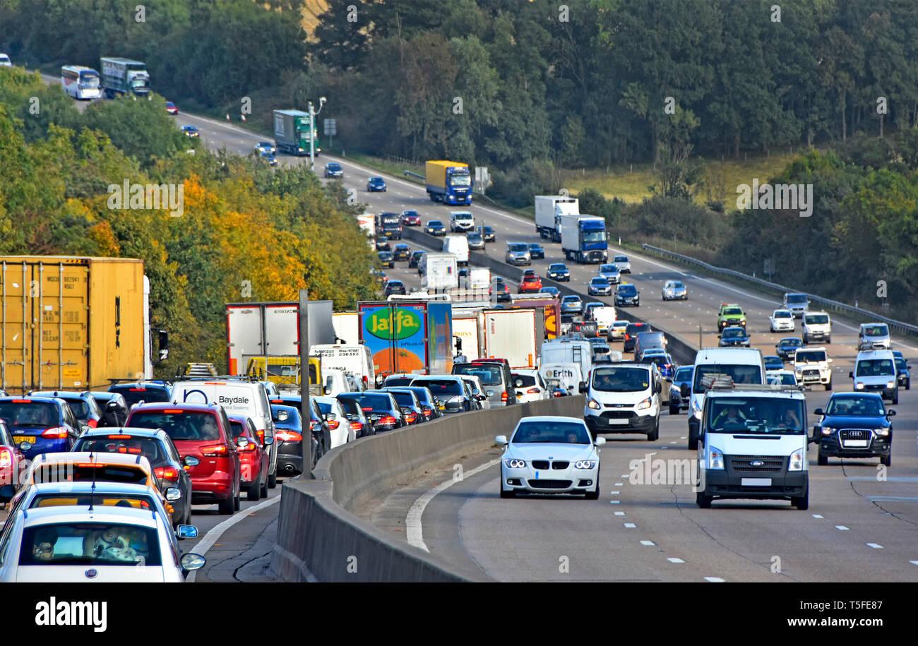 Rush hour on M25 UK motorway queue of cars trucks & lorries in traffic jam in hilly rural countryside section of London orbital highway England UK - Stock Image