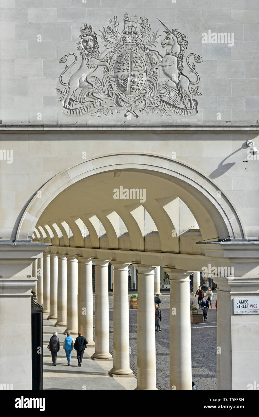 Tourists stroll below Coat of Arms at Royal Opera House shopping arcade with colonnade forming part of the complex at Covent Garden London England UK Stock Photo