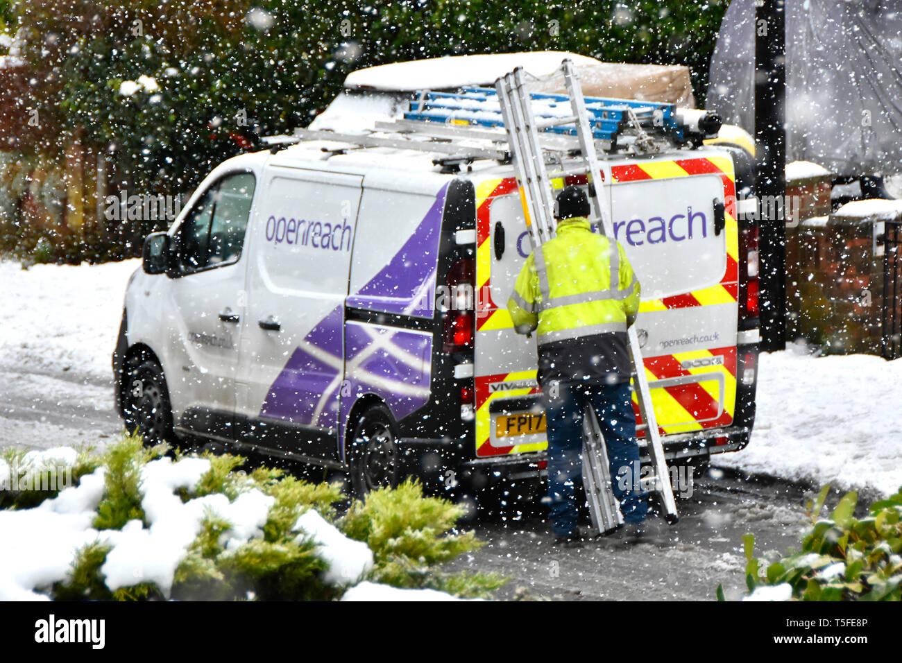 Winter weather snowy street scene snowflakes around BT Openreach van & engineer high vis jacket working with ladder in falling snow storm England UK - Stock Image