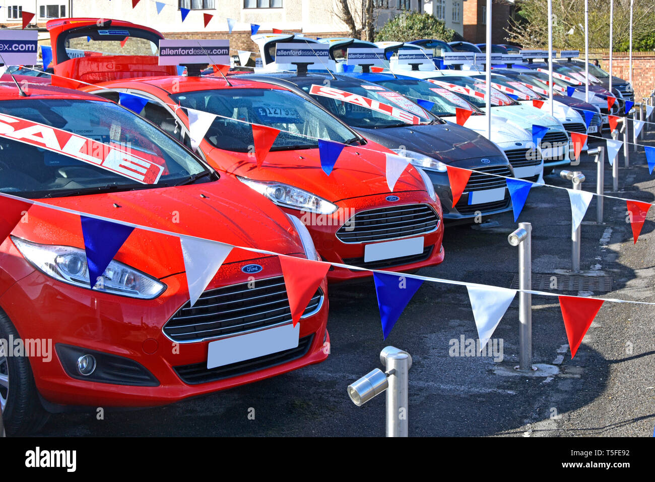 Sale poster at Ford car dealership business forecourt display of used second hand red white & blue cars & bunting in dealer sales promotion England UK - Stock Image
