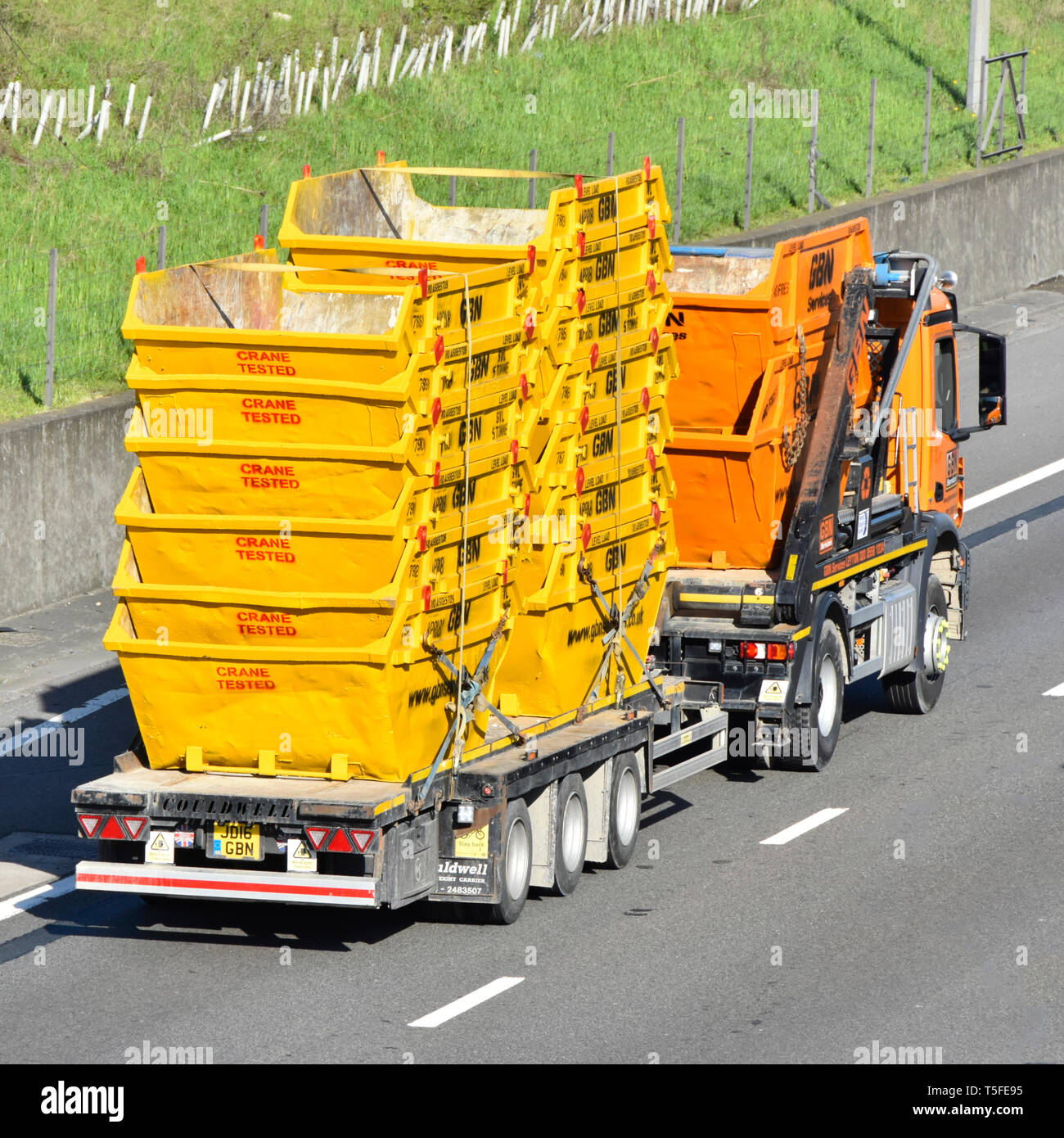 Skip lorry truck towing a trailer loaded with delivery of thirteen empty yellow industrial steel rubbish skip bins marked as crane tested uk motorway - Stock Image