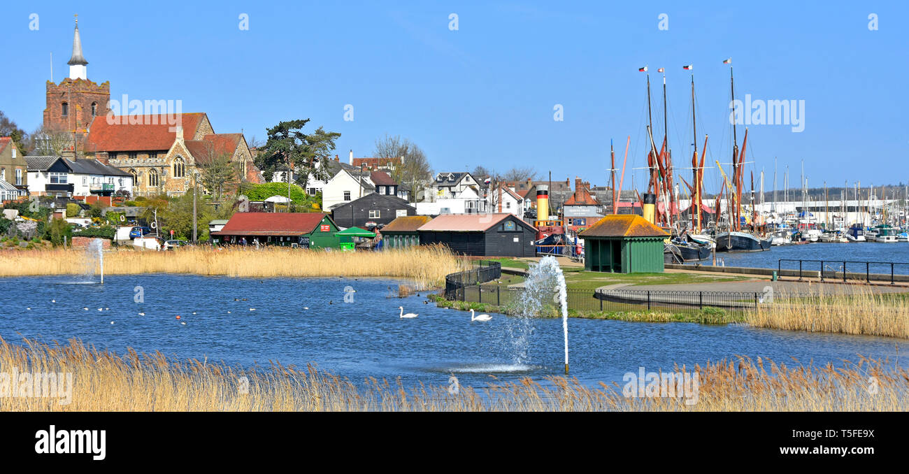 Pond & fountain landscape in Promenade Park beside River Blackwater estuary church & masts of Thames sailing barges beyond in Maldon Essex England UK - Stock Image
