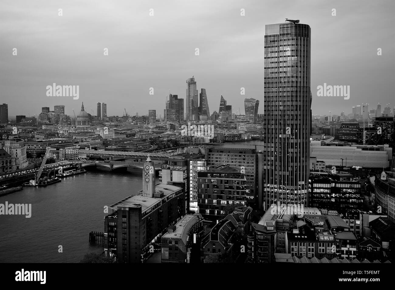 London skyline at dusk showing the river and other landmarks. - Stock Image