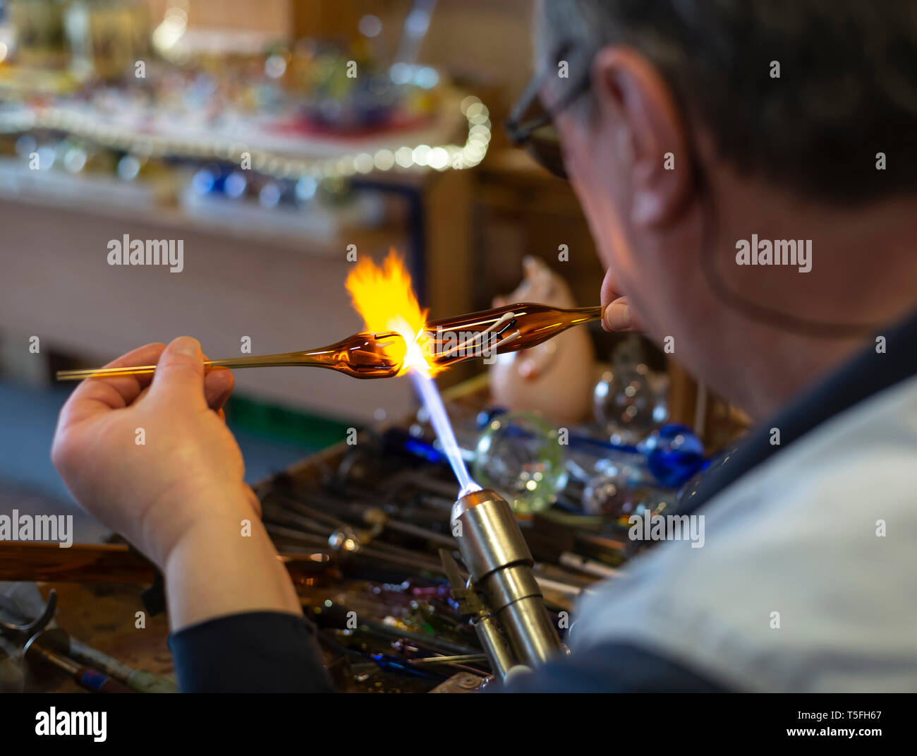 Glass blower forming melting glass - Stock Image