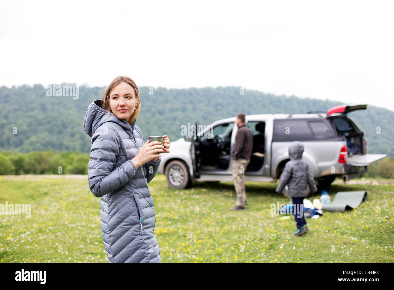 In the foreground, a woman with a cupboard in the background is an SUV with open trunk and a man with a child unloads the car - Stock Image