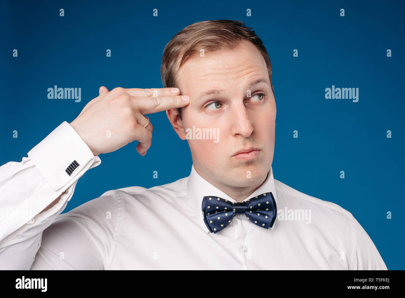 Man wearing white shirt and bow tie showing sign of pistol - Stock Image