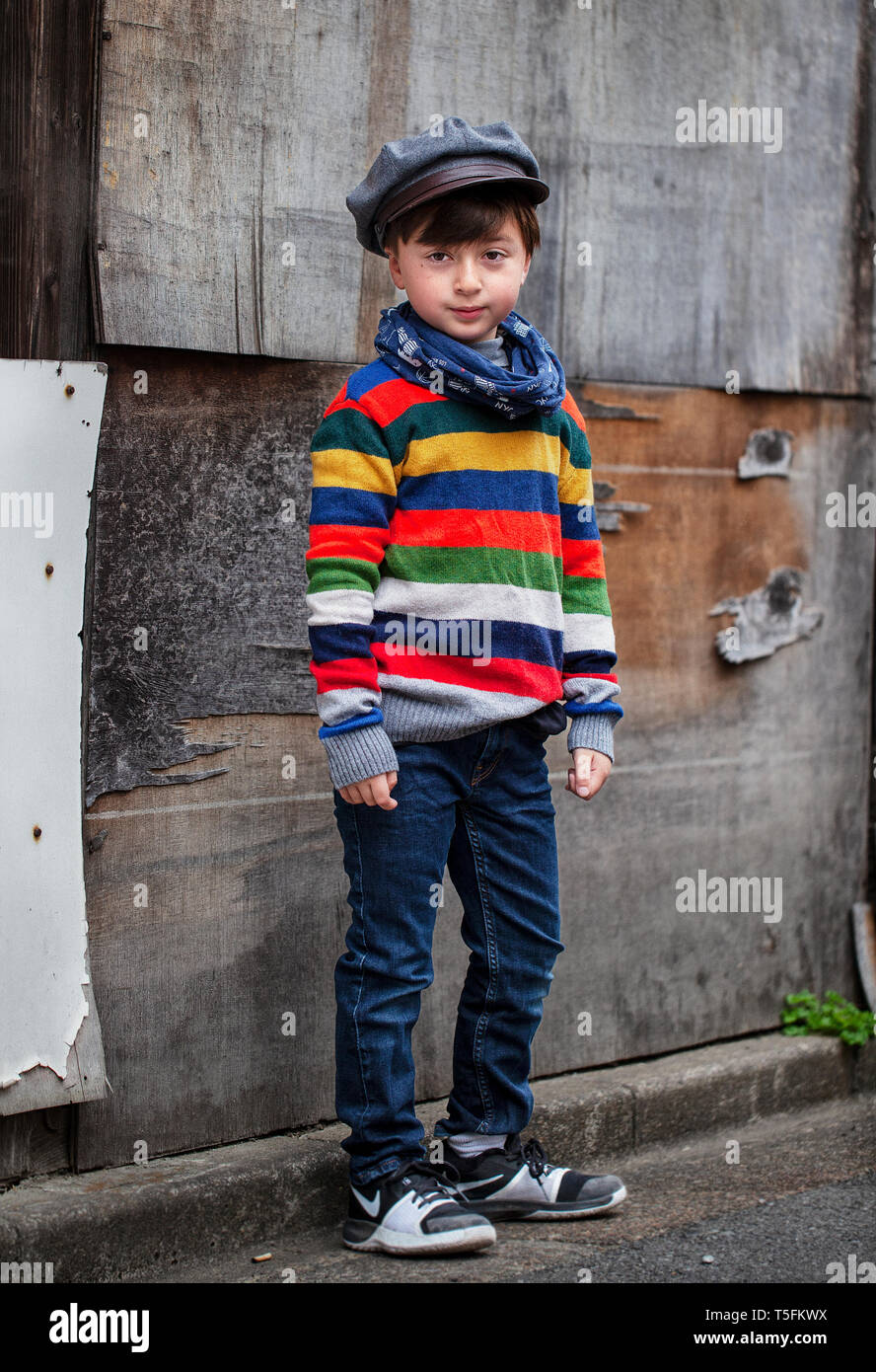 Mixed race Asian Caucasian boy wearing a rainbow striped sweater and gray cap and blue denim jeans in front of a dilapidated wood building Stock Photo