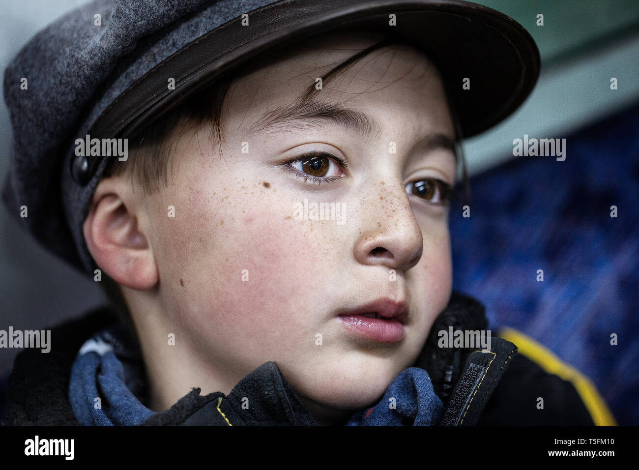 Mixed race Asian Caucasian boy in gray hat and blue scarf with red cheeks from the cold winter air - Stock Image
