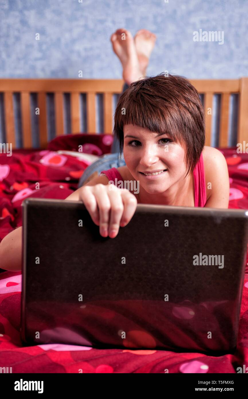 Junge Frau liegt auf ihrem Bett mit einem Leptop vor sich vor sich und schaut in die freundlich in die Kamera. - Stock Image