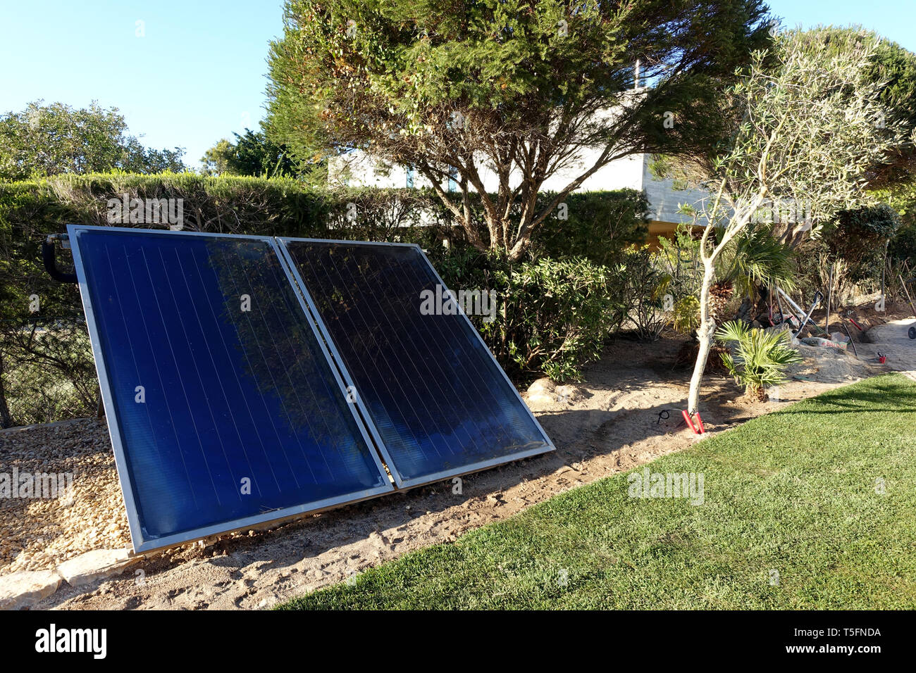 Solar panels in front garden of house - Stock Image