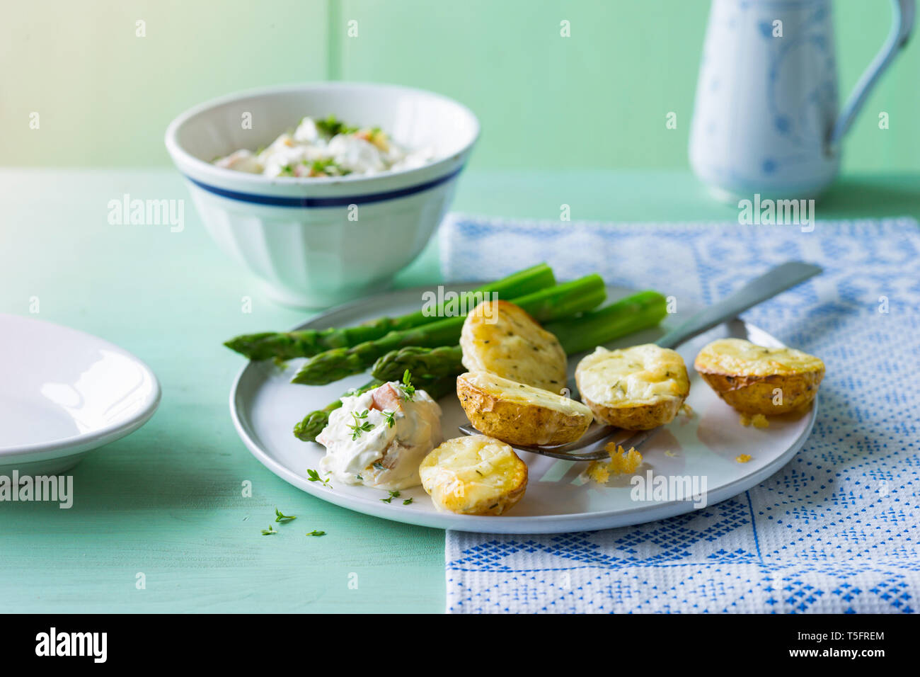 Baked potatoes with green asparagus and cream cheese, gratinated with cheese - Stock Image