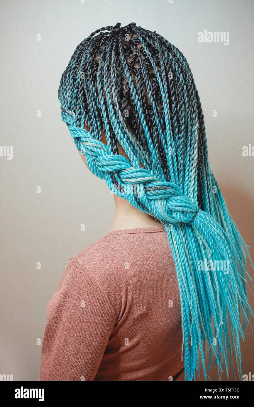 braids Senegalese braids are intertwined to the girl's hair, blue braids, hair in the African style - Stock Image